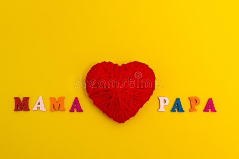 在黄色背景的红色被编织的心脏,妈妈爱爸爸 免版税库存图片