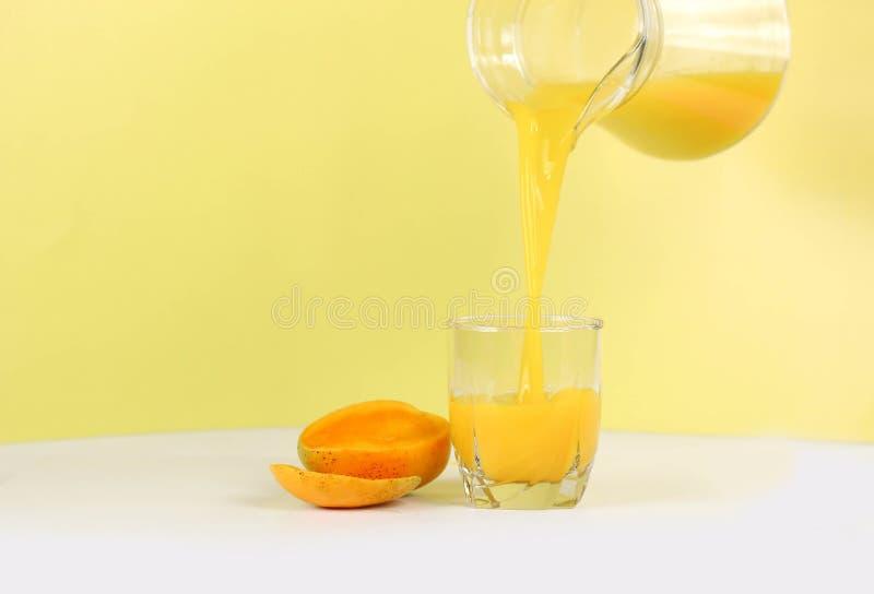 在黄色背景的芒果汁 库存照片
