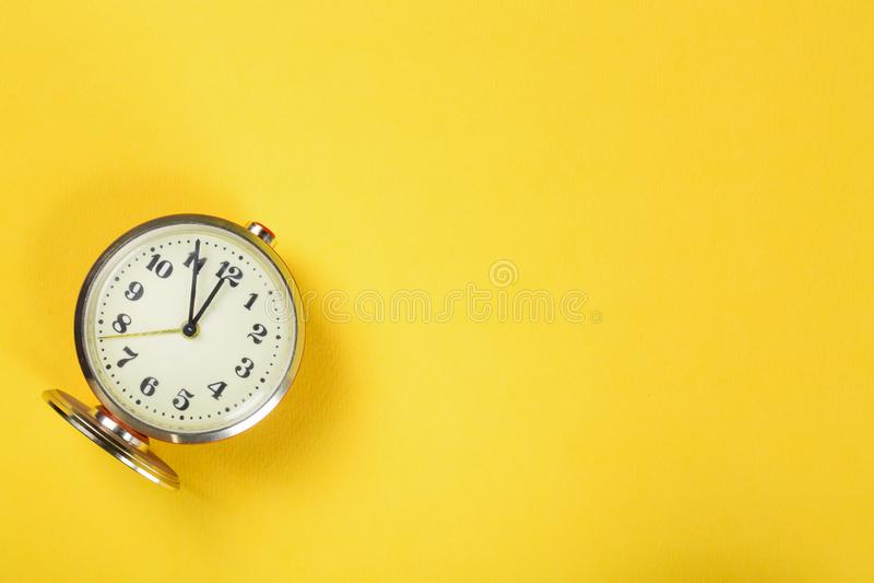 在黄色背景的葡萄酒闹钟与拷贝空间 免版税库存照片