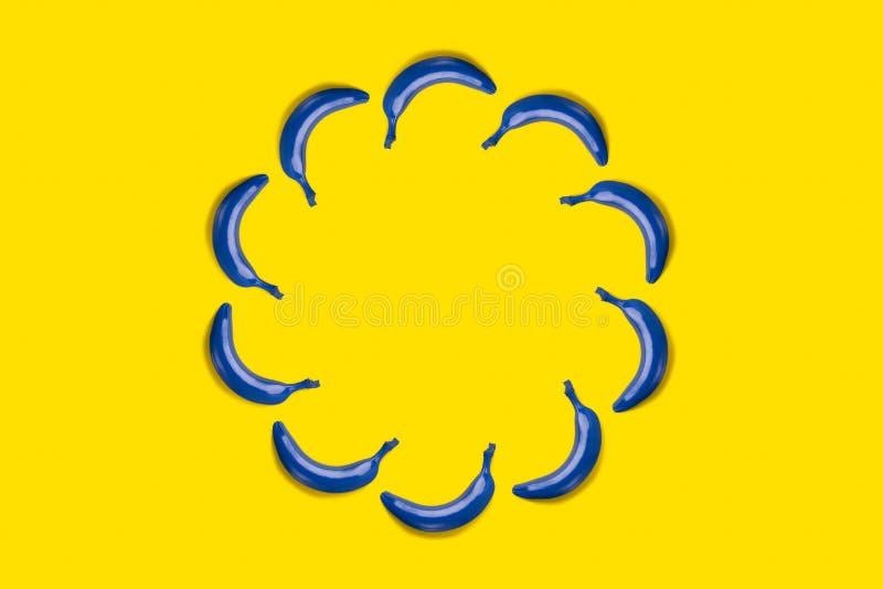 在黄色背景的蓝色香蕉 库存图片