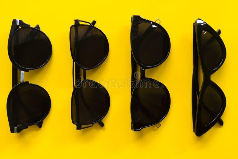 在黄色背景空的空间的太阳镜 免版税库存照片