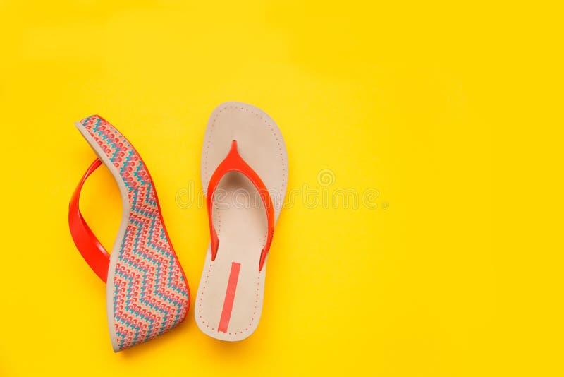 在黄色背景隔绝的明亮的夏天妇女` s凉鞋 顶视图 免版税库存照片