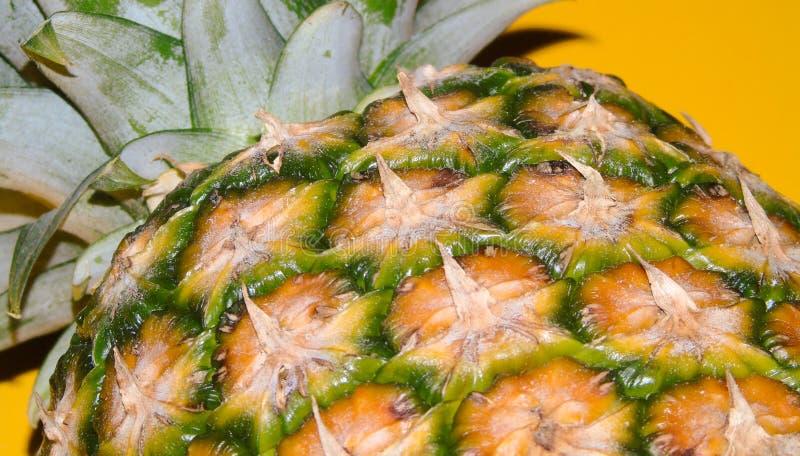 在黄色背景,鲜美和刷新的果子隔绝的一个成熟菠萝的特写镜头,健康食品,细节 免版税库存照片