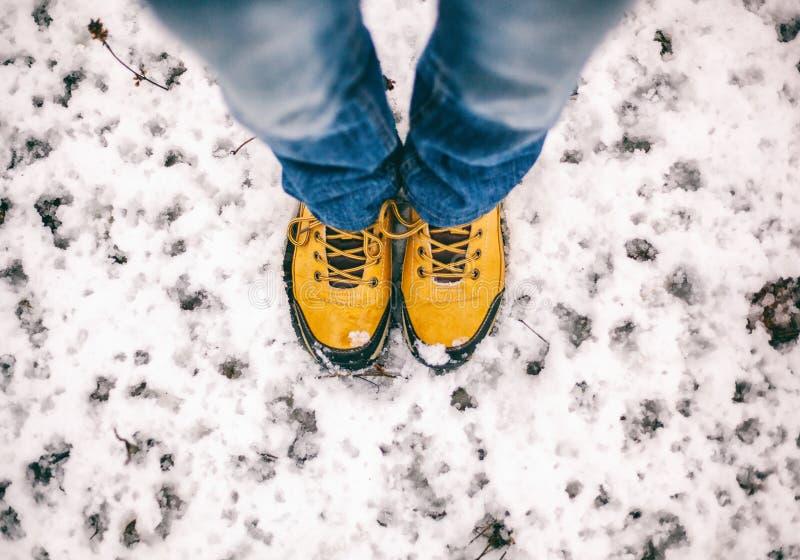 在黄色迁徙的起动的脚在雪,一次旅行在冬天, pictu 免版税库存图片