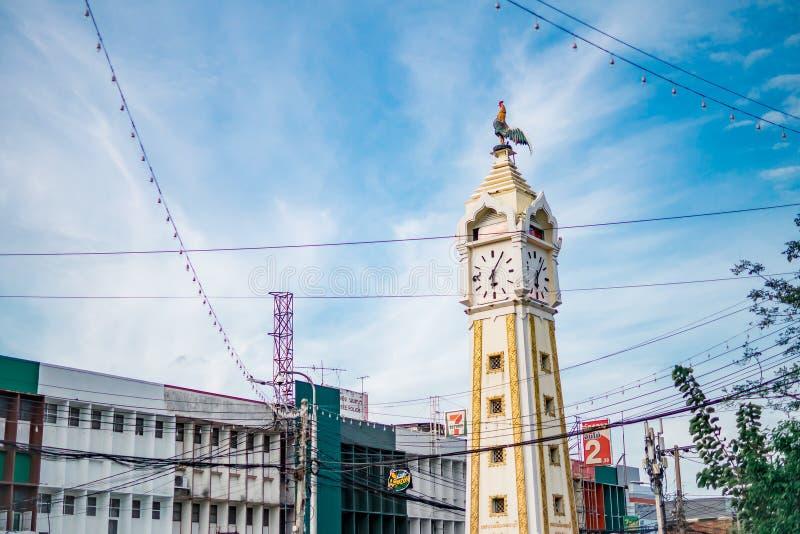 在黄色钟楼的鸡雕象与反对天空蔚蓝的一根杂乱电导线 免版税库存照片