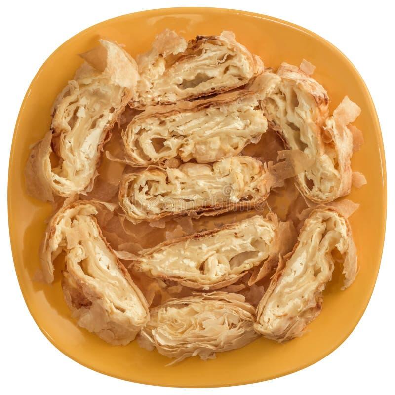 在黄色陶瓷板材提供的塞尔维亚传统乳酪卷饼Gibanica切片隔绝在白色背景 免版税库存图片