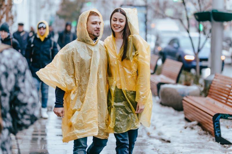 在黄色雨衣和他的女朋友打扮的人在街道上在雨中走 免版税库存照片