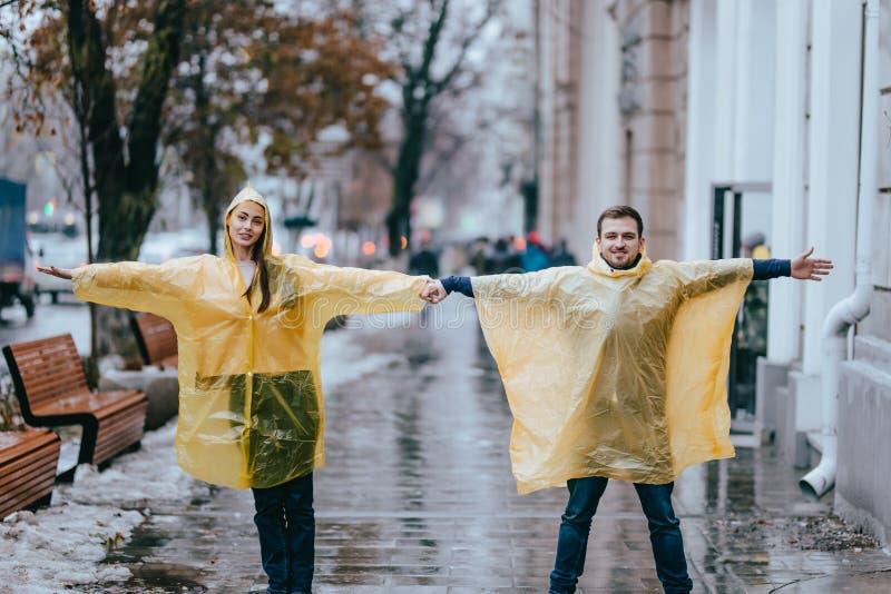 在黄色雨衣和女孩打扮的爱的人在街道上在雨中站立 免版税图库摄影