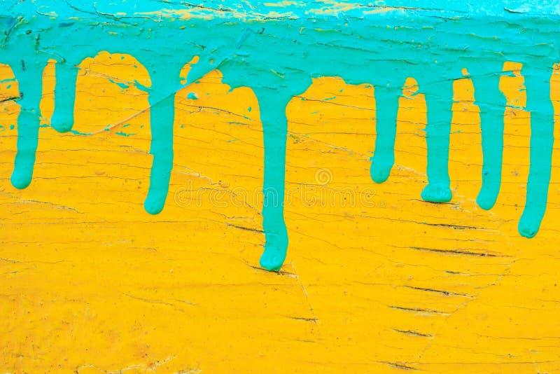 在黄色,老破裂的油漆背景纹理的滴下的绿色油漆 库存照片