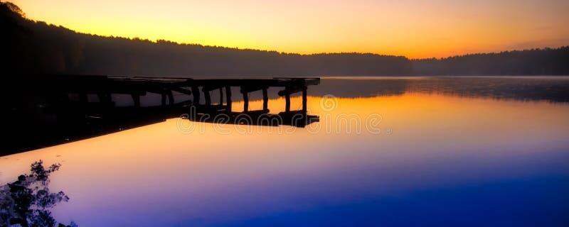 在黎明前的充满活力的颜色天空在湖附近 库存图片