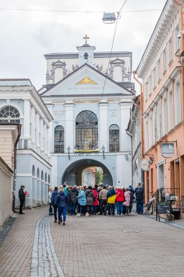 在黎明附近门的游人在维尔纽斯,我们的黎明门的夫人教堂是在玻璃窗后的中部 库存图片