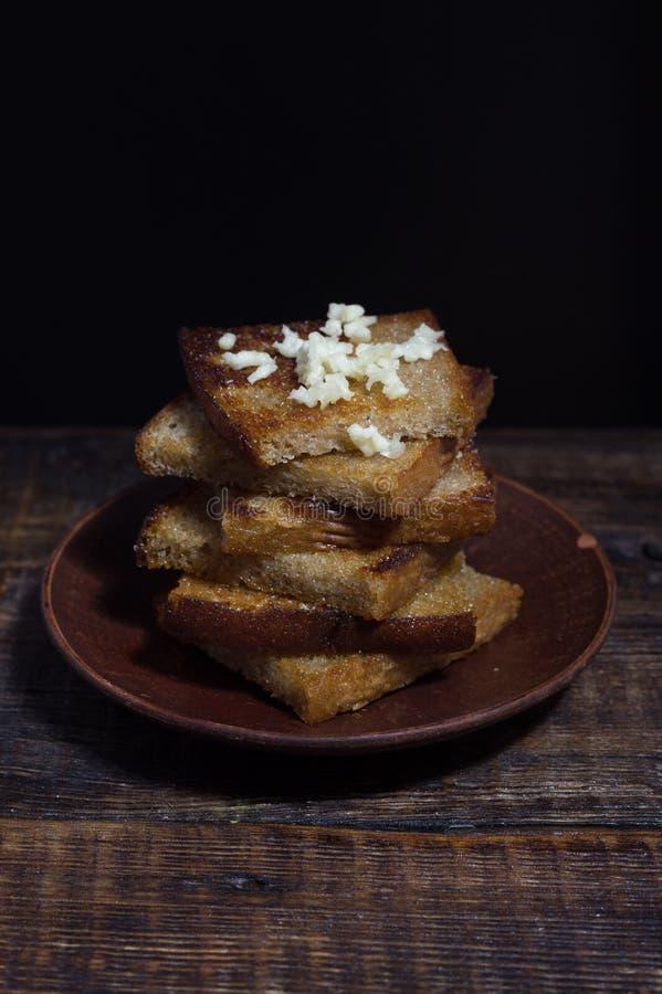 在黏土板材的油煎方型小面包片 多士用大蒜 免版税库存照片
