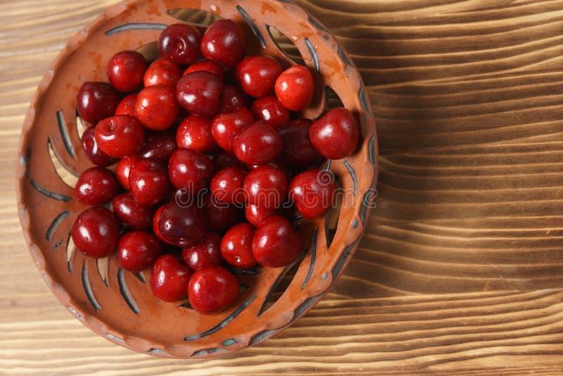 在黏土板材的红色甜樱桃在一张木桌上 免版税图库摄影