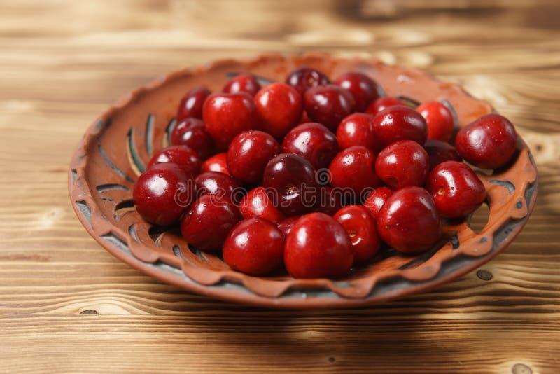 在黏土板材的红色甜樱桃在一张木桌上 图库摄影