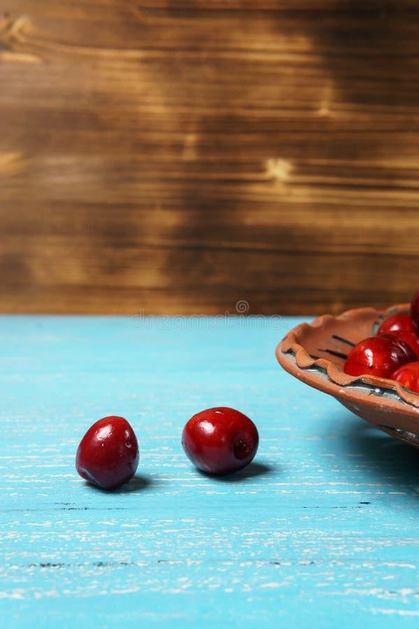 在黏土板材的红色甜樱桃在绿松石木桌上 图库摄影