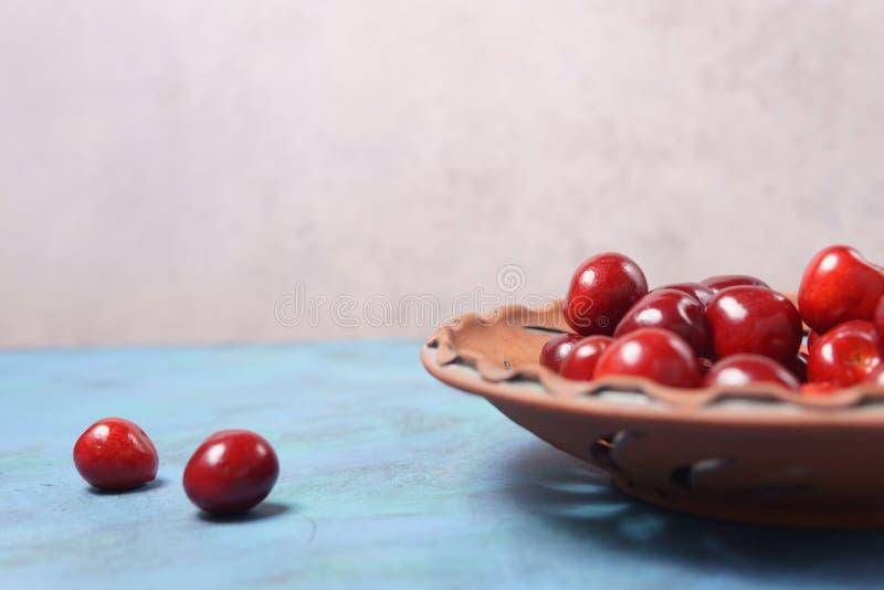 在黏土板材的红色甜樱桃在绿松石桌上 免版税库存照片