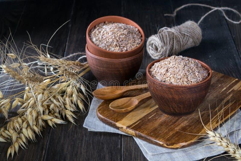 在黏土碗的麦子,燕麦麦子和燕麦的麸皮和耳朵 改进消化的膳食补充剂 库存图片