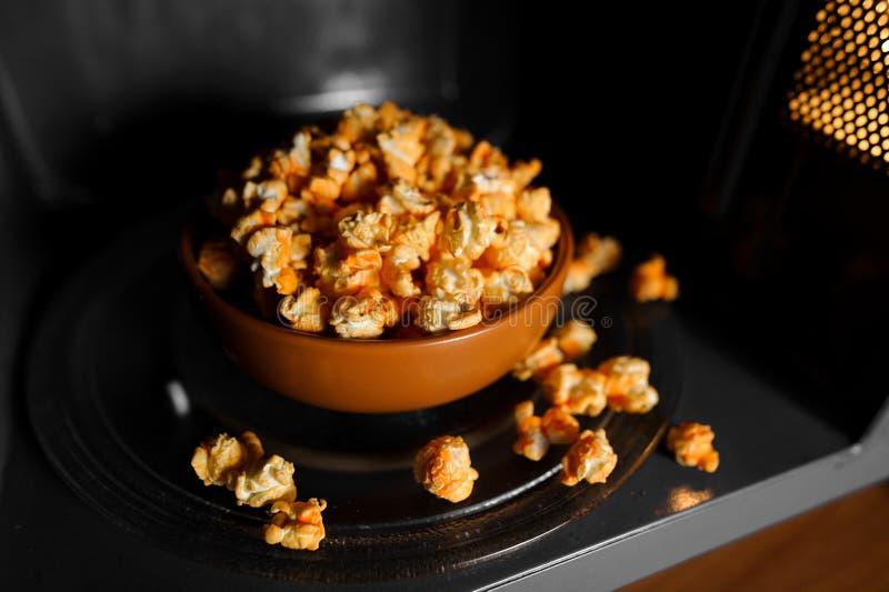 在黏土褐色盘立场的烤玉米花在微波 免版税库存照片