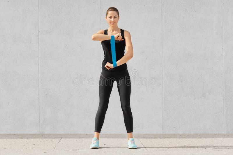 在黑上面打扮的精力充沛的妇女和绑腿,sportshoes,伸有健身胶的手,为竞争,isolat做准备 免版税库存照片