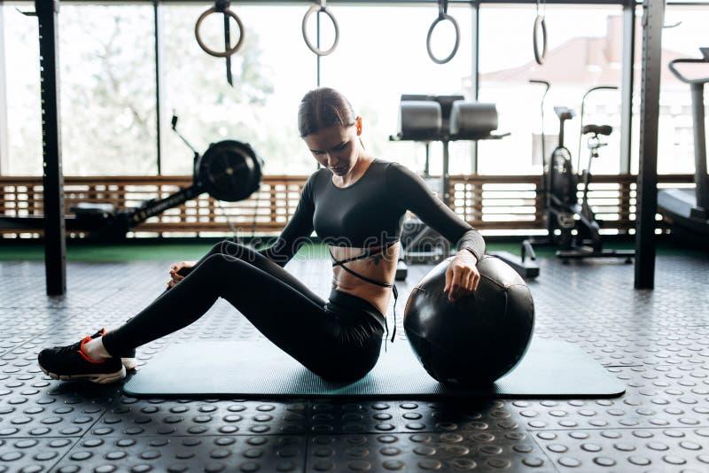在黑体育衣裳打扮的亭亭玉立的深色头发的女孩在健身房的健身球旁边坐健身的席子 免版税库存图片