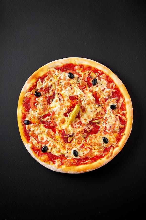 在黑具体背景,顶视图的热的意大利辣香肠烘饼 免版税库存图片