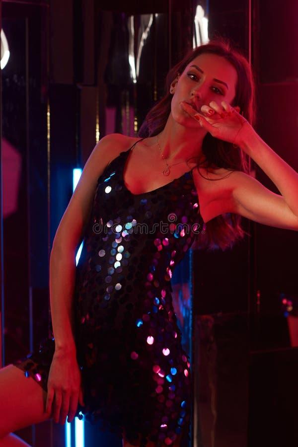 在黑发光的cami礼服的女性模型坐大立方体和 库存图片