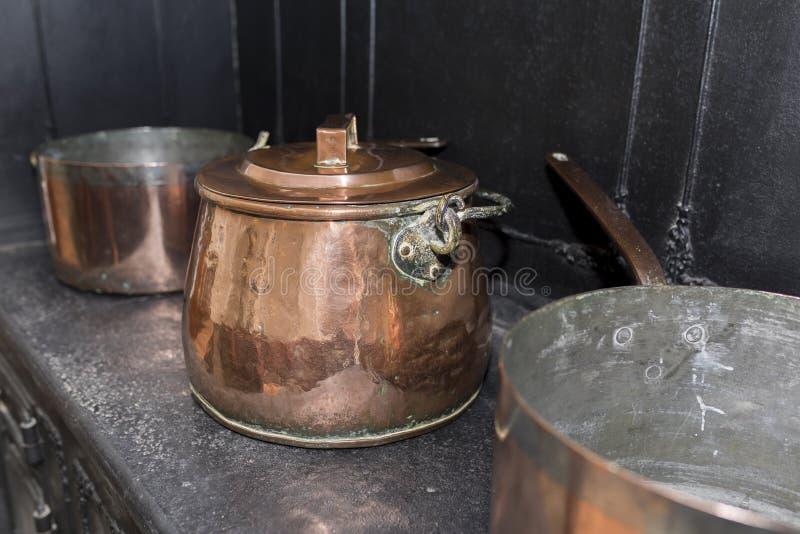 在黑古色古香的煤气炉的维多利亚女王时代的铜砂锅平底锅在a 免版税库存图片