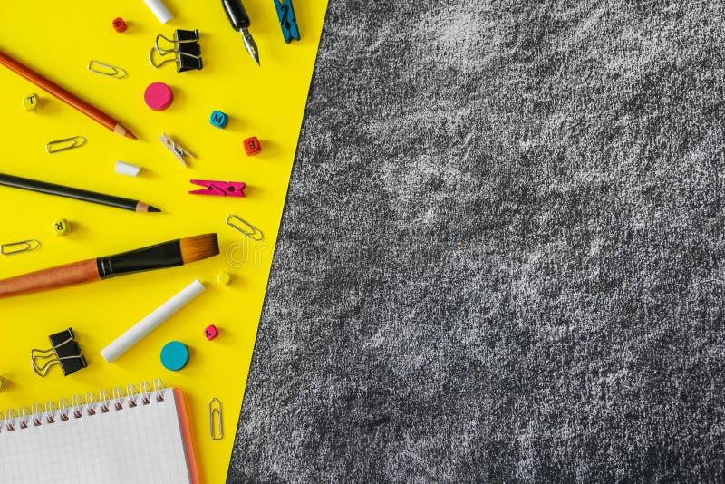 在黑和黄色黑板背景的多彩多姿的学校用品与拷贝空间 免版税库存照片