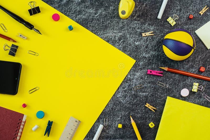 在黑和黄色黑板背景的多彩多姿的学校用品与拷贝空间 图库摄影