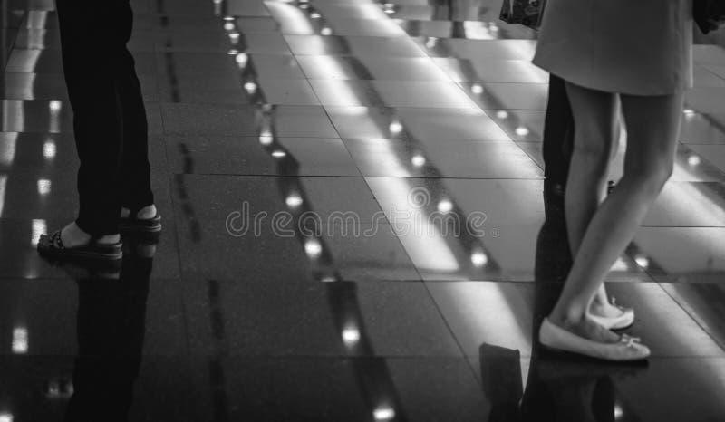 在黑地板上站立在商城或客栈的妇女腿的选择聚焦 城市点燃晚上场面 免版税库存照片