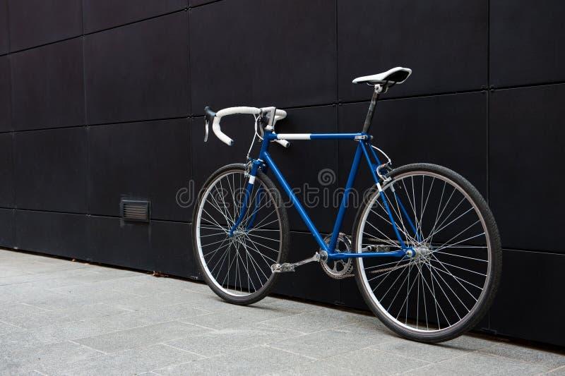 在黑墙壁上的葡萄酒蓝色城市自行车 免版税库存图片