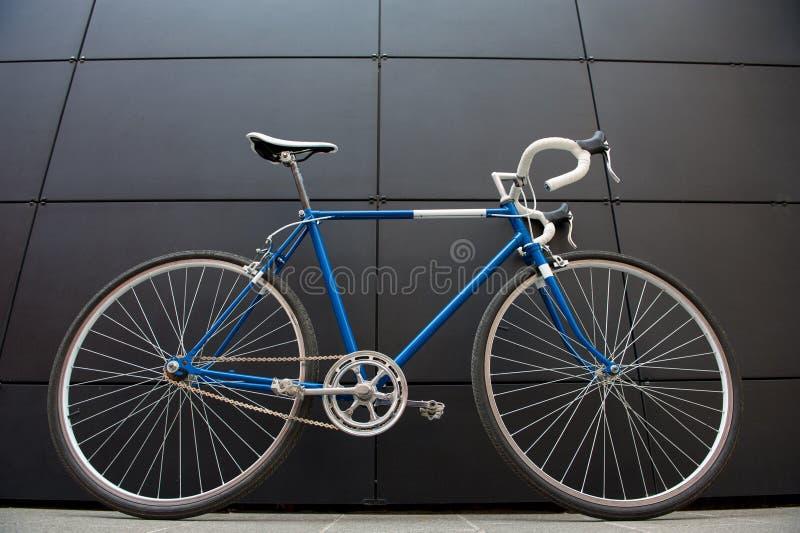在黑墙壁上的葡萄酒蓝色城市自行车 库存图片