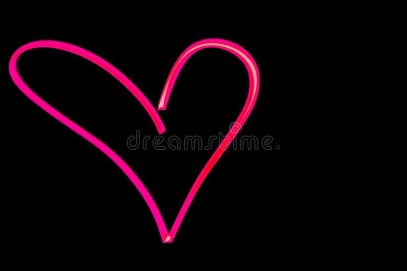 在黑夜空的桃红色心脏概述光绘画 库存照片