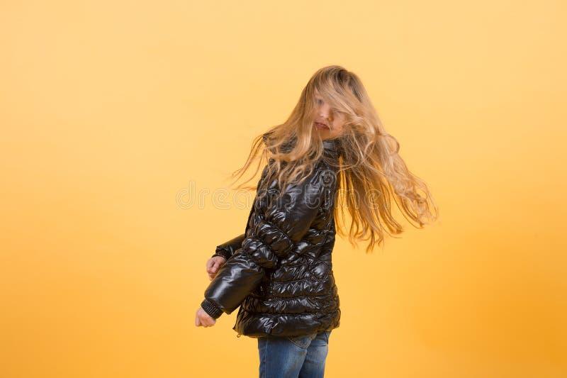 在黑夹克的孩子女孩震动长的金发 库存照片