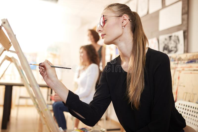 在黑女衬衫和牛仔裤穿戴的玻璃的好少女坐在画架并且绘在图画的一幅画 库存照片