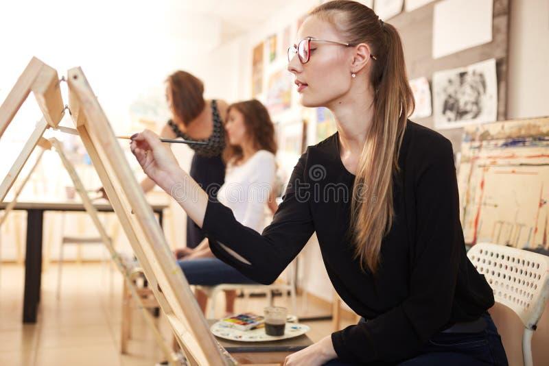 在黑女衬衫和牛仔裤穿戴的玻璃的好少女坐在画架并且绘在图画的一幅画 免版税库存照片