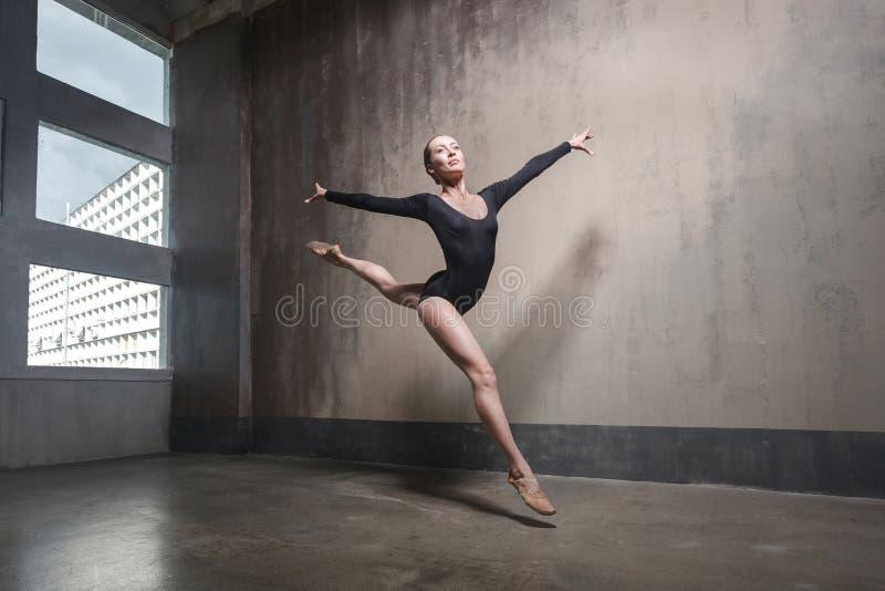 在黑实践芭蕾位置的美丽的优美的ballerine 免版税库存图片