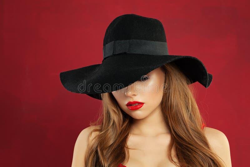在黑帽会议的俏丽的年轻女人时装模特儿在红色背景 库存图片