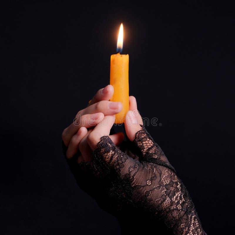 在黑手套的女性手举一个灼烧的蜡烛 特写镜头 黑色墙壁背景 方形框架 题材假日万圣夜 神秘主义者 免版税库存照片