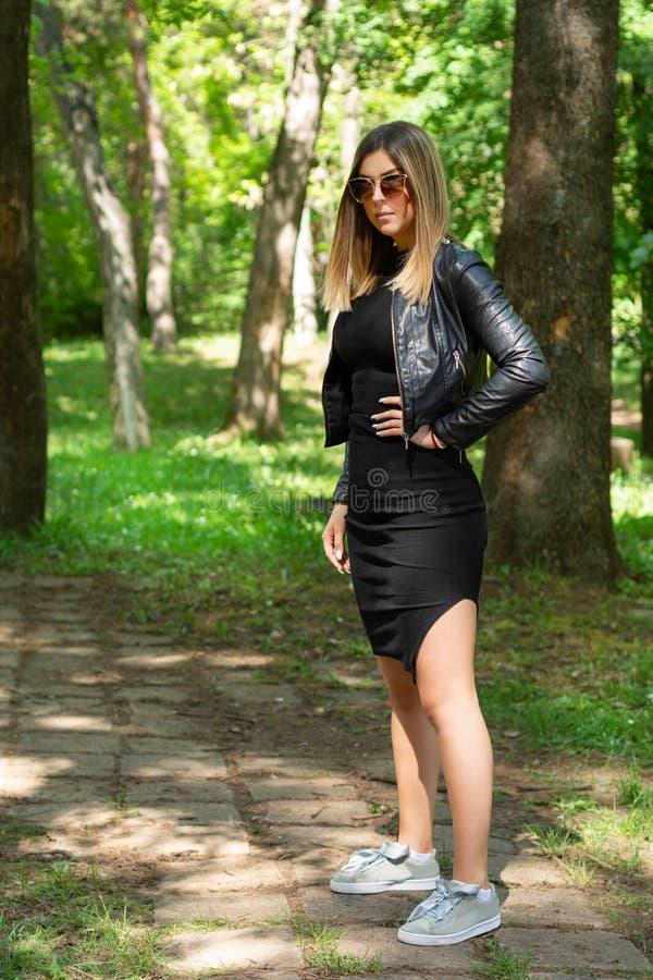 在黑摆在本质上的礼服的有吸引力的妇女模型和皮夹克和太阳镜在一个晴朗的春日用在臀部的手 免版税库存图片