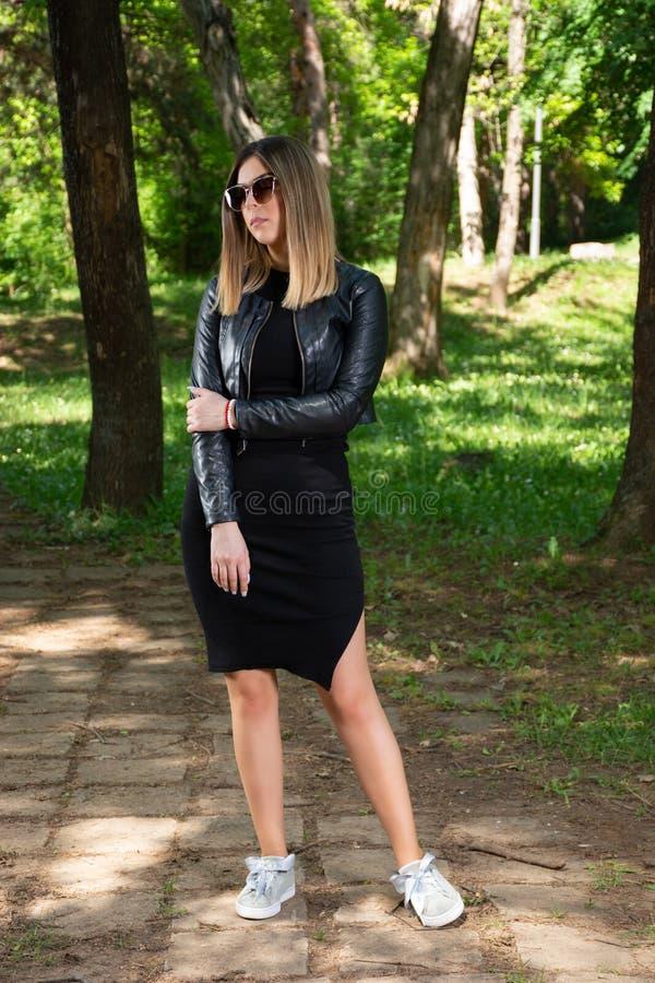 在黑摆在本质上的礼服的有吸引力的时尚女孩模型和皮夹克和太阳镜在一个晴朗的春日 库存照片