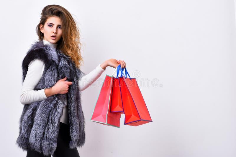 在黑星期五,销售和折扣 女孩构成面孔穿戴毛皮背心白色背景 妇女购物的豪华精品店 库存图片