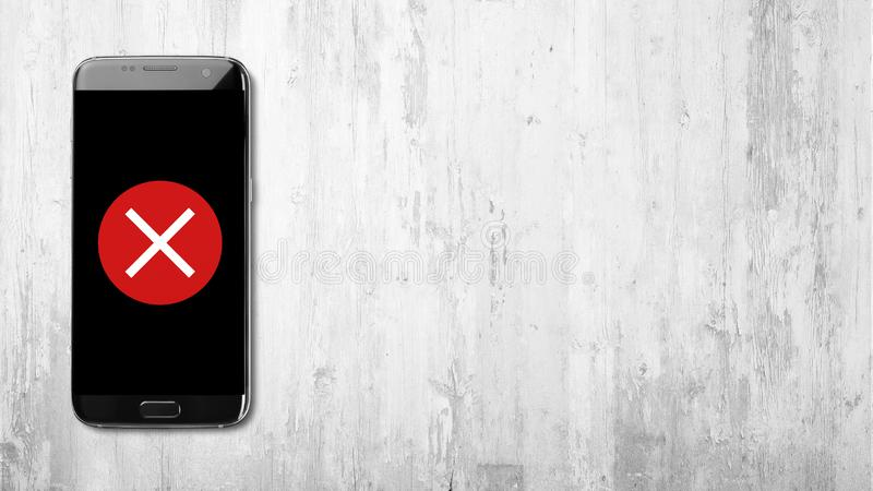 在黑智能手机的发怒象在白色木背景 免版税库存图片