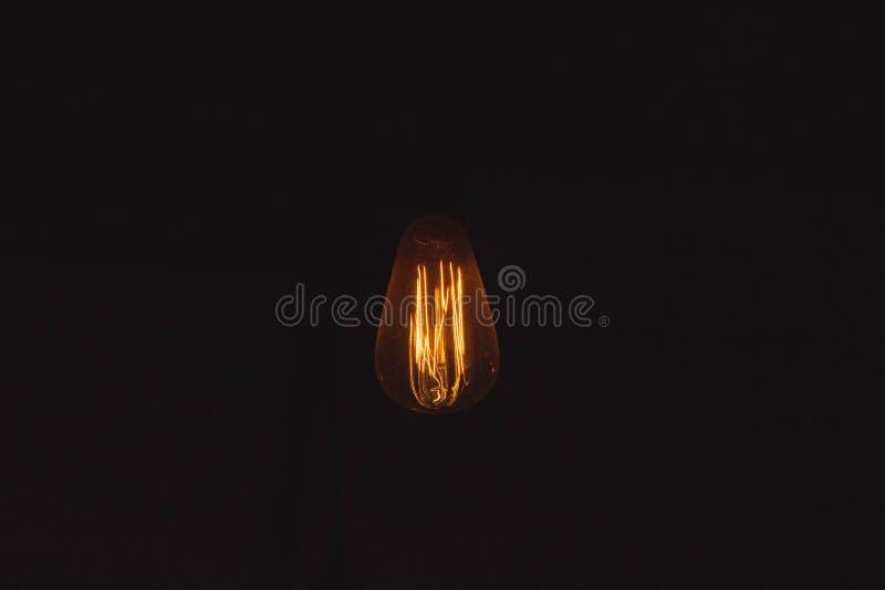 在黑暗点燃的一个昏暗的电灯泡 免版税库存图片