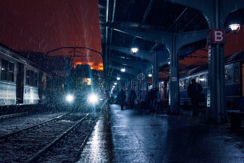 在黑暗的人的剪影在平台的一个火车站 库存照片