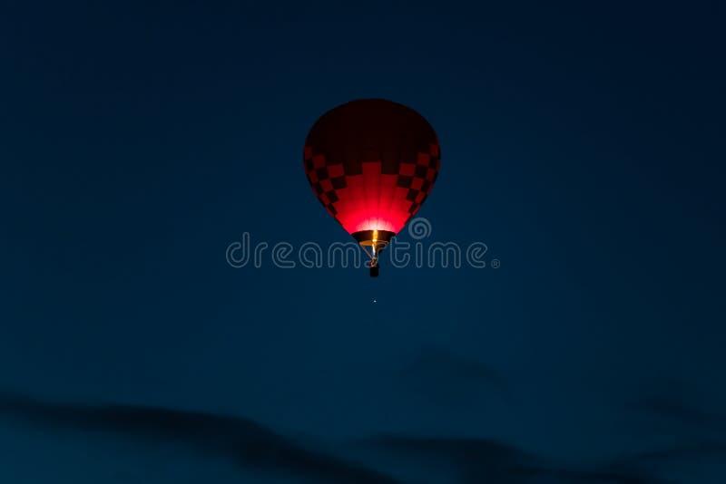 在黑暗的发光在深蓝清早天空的桃红色和紫色颜色的五颜六色的热空气气球 库存图片