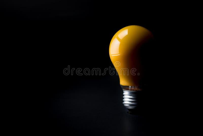 在黑暗的发光的电灯泡 创造性启发概念 免版税库存照片