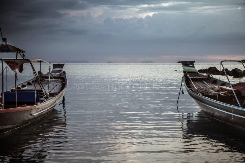 在黑暗的喜怒无常的日落期间,亚洲生活方式风景传统亚洲小船将天际指向在风平浪静 免版税库存照片