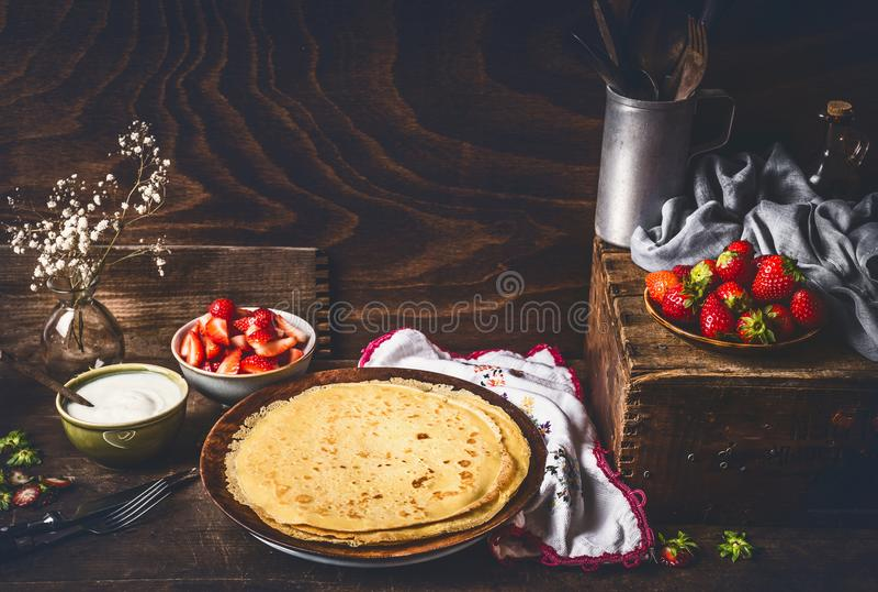 在黑暗的土气厨房用桌上的自创绉纱用草莓和酸奶在碗 免版税库存照片