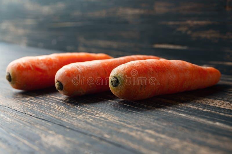 在黑暗的土气木背景的三棵红萝卜 图库摄影